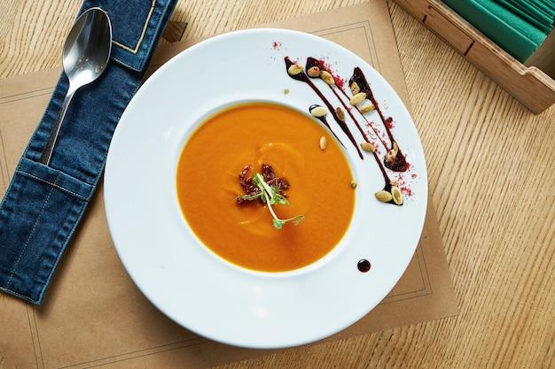 Zuppa di zucca fresca e vegetariana con crema in un piatto bianco su un tavolo di legno. tavolo da ristorante