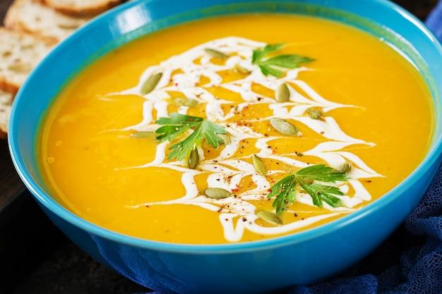 Zuppa di zucca in una ciotola servita con prezzemolo e semi di zucca. zuppa vegana cibo del giorno del ringraziamento. pasto di halloween.