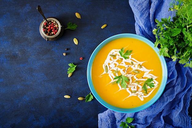 Zuppa di zucca in una ciotola servita con prezzemolo e semi di zucca. zuppa vegana cibo del giorno del ringraziamento.