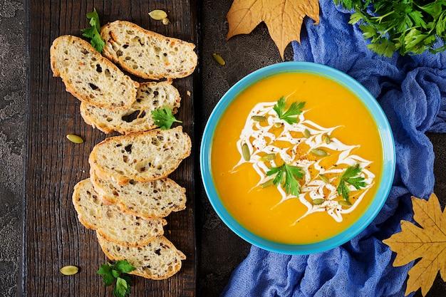 Zuppa di zucca in una ciotola servita con semi di zucca e prezzemolo. zuppa vegana