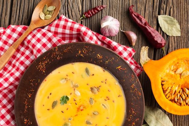 Zuppa di zucca piatta distesa e cucchiaio di legno con ingredienti