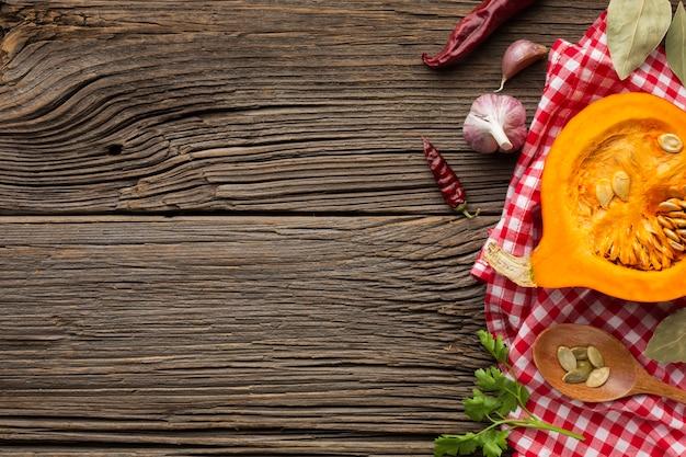 Zuppa di zucca piatto disteso e cucchiaio di legno con ingredienti e copia spazio