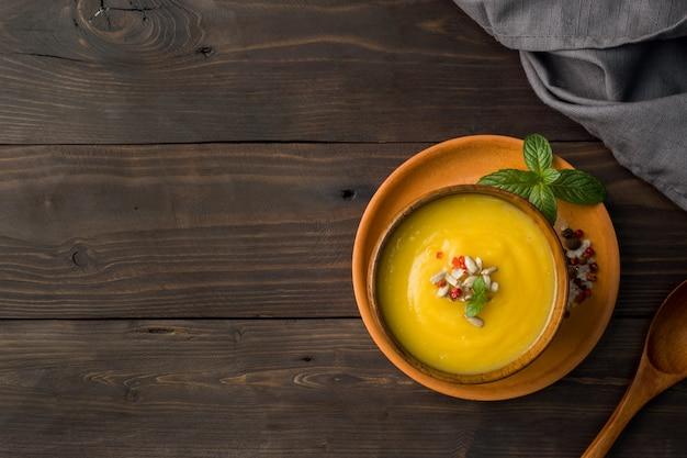 Zuppa di zucca schiacciata con spezie in ciotole di legno su sfondo scuro bordo