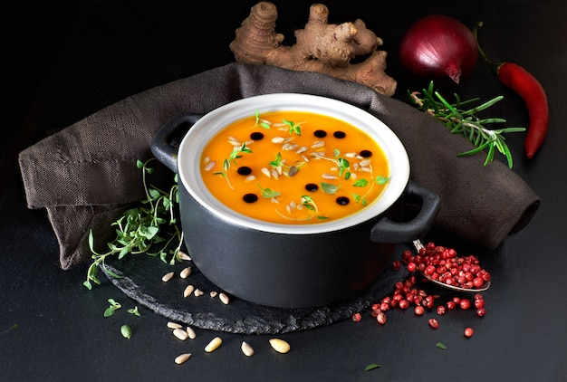 Zuppa di zucca speziata servita in padella in ceramica con olio di zucca e semi di girasole