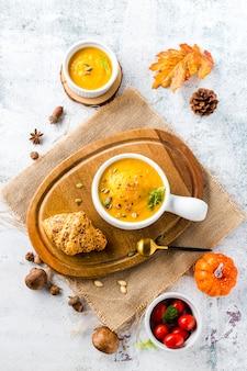 Zuppa di zucca vista dall'alto sulla tavola di legno circondata da verdure autunnali