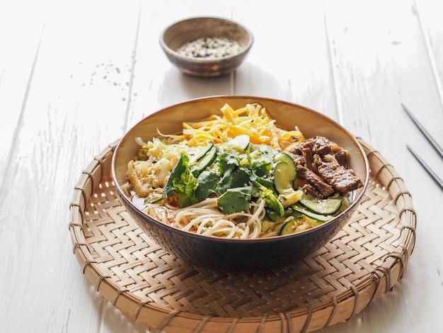 Zuppa fredda di kuksi coreano con verdure, uova strapazzate, manzo e noodles in una ciotola e bacchette