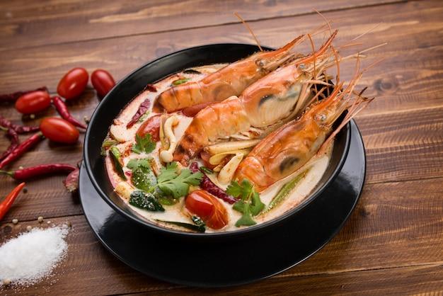 Zuppa piccante acida di tom yum goong sul piano d'appoggio di legno che osserva alimento locale tailandese