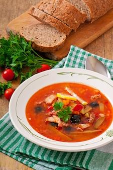 Zuppa solyanka russa con carne, olive e cetriolini in ciotola di legno