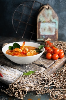 Zuppa tom yam con gamberetti, calamari e peperoncino su tavola di legno testurizzata.