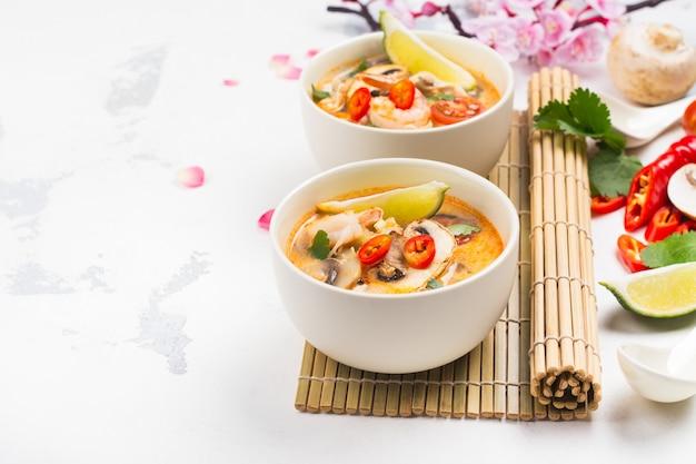 Zuppa tom yum tradizionale con ramo di sakura in fiore sul tavolo di pietra bianca