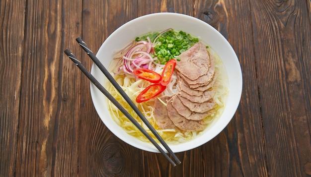 Zuppa vietnamita tradizionale pho bo con carne, spaghetti di riso, zuppa asiatica in una ciotola con le bacchette. spazio per il testo. vista dall'alto. zuppa asiatica pho bo sul fondo della tavola in legno.