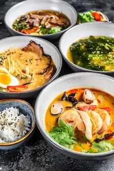 Zuppe asiatiche in ciotole su una tavola nera