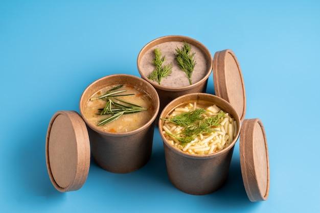 Zuppe di funghi, pollo e piselli in bicchieri usa e getta di carta da asporto
