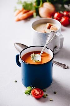 Zuppe ed ingredienti del pisello e del pomodoro su fondo concreto