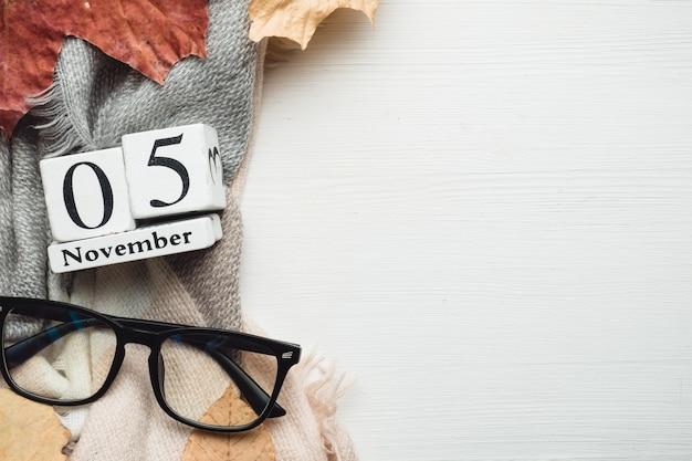 05 de novembro em calendário feito de cubos brancos com folhas e óculos. postura plana