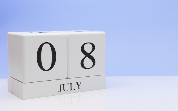 08 de julho. dia 8 do mês, calendário diário na mesa branca com reflexão, com a luz de fundo azul. horário de verão, espaço vazio para texto