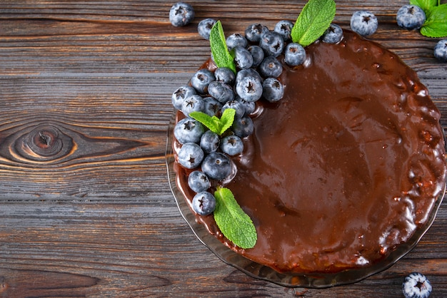 1 bolo de chocolate com mirtilos frescos e hortelã em uma superfície de madeira marrom escura, torta, vista de cima