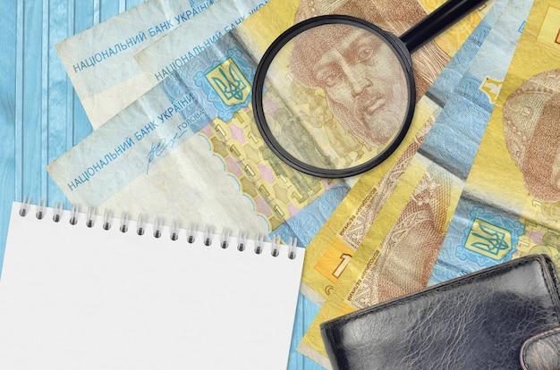 1 contas de hryvnia ucranianas e lupa com bolsa preta e bloco de notas. conceito de dinheiro falso. procure diferenças em detalhes em notas de dinheiro para detectar dinheiro falso