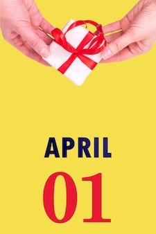 1º de abril. calendário vertical festivo com as mãos segurando uma caixa de presente branca com fita vermelha e data do calendário 1 de abril na iluminação de fundo amarelo. mês de primavera, dia do conceito de ano.