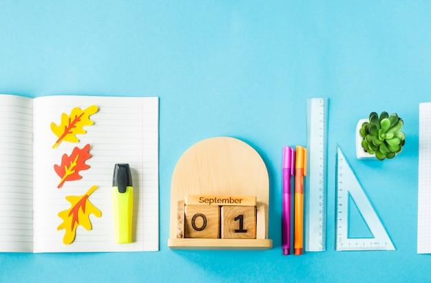 1 de setembro em um calendário de madeira entre os suprimentos para estudo sobre um fundo azul
