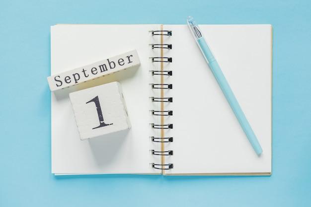 1º de setembro em um calendário de madeira no livro de estudo em azul. volta ao conceito de escola