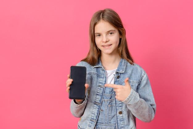 1 linda garota branca de 10 anos em uma jaqueta jeans azul com um smartphone nas mãos em uma superfície rosa
