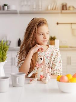 1 menina europeia branca de 10 anos na cozinha à mesa com ovos de páscoa e um coelho de brinquedo
