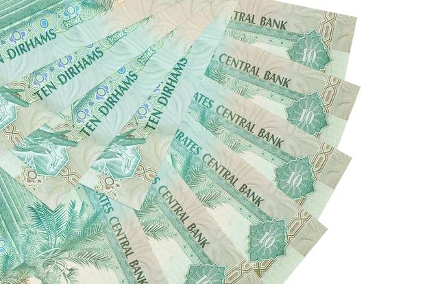 10 contas de dirhams dos emirados árabes unidos encontram-se isoladas na parede branca com espaço de cópia empilhados em forma de leque close-up. conceito de transações financeiras