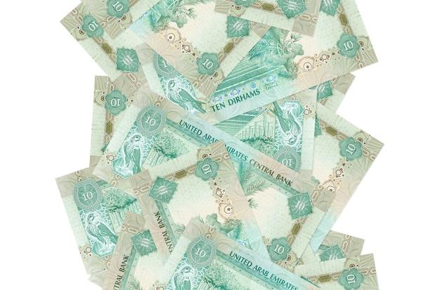 10 contas de dirhams dos emirados árabes unidos voando baixo isolado no branco. muitas notas caindo com espaço de cópia em branco no lado esquerdo e direito