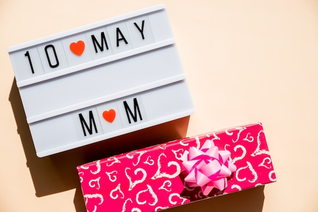10 de maio cartão de dia das mães com pequenas corações vermelhos em fundo pastel. feriado, cartão de felicitações. conceito de dia das mães. melhor mãe do mundo