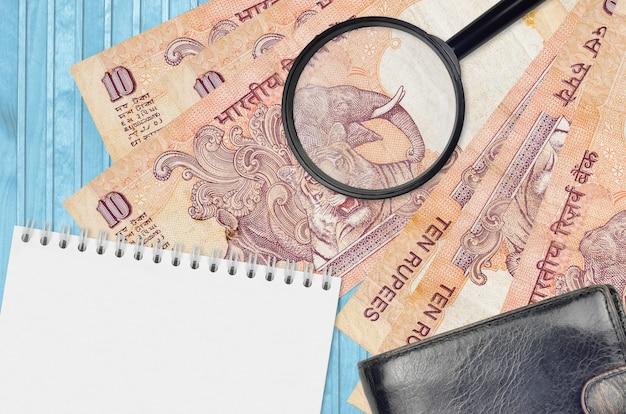 10 notas de rúpias indianas e lupa com bolsa preta e bloco de notas