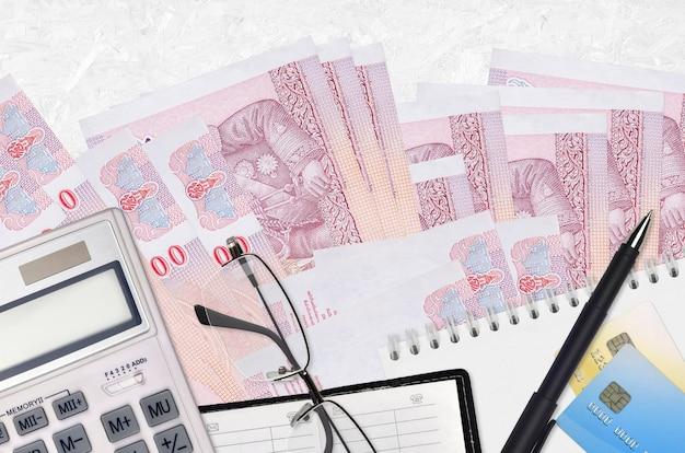 100 contas de baht tailandês e calculadora com óculos e caneta
