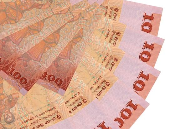 100 contas de rúpias do sri lanka encontram-se isoladas na parede branca com espaço de cópia empilhados em forma de leque close-up. conceito de transações financeiras
