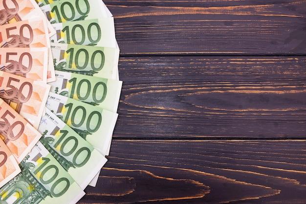 100 e 50 euros dispostos sobre um fundo de madeira. copie o espaço.