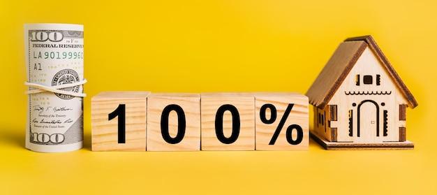100 juros com modelo em miniatura de casa e dinheiro em um fundo amarelo. o conceito de negócios, finanças, crédito, impostos, imobiliário, casa, habitação