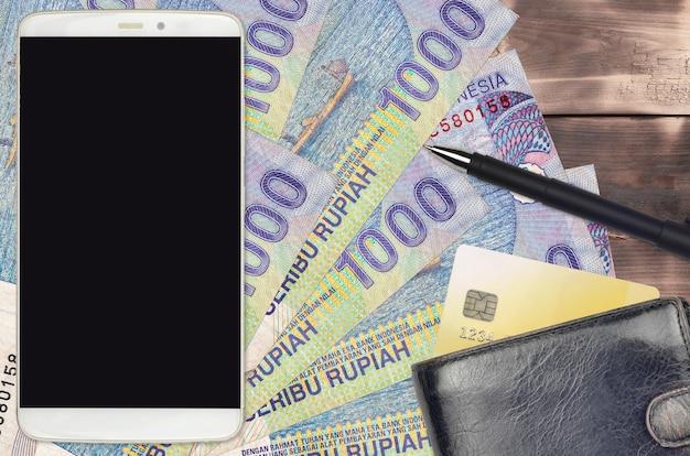 1000 contas de rupias indonésias e smartphone com bolsa e cartão de crédito