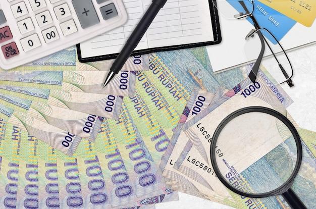 1000 notas de rupias indonésias e calculadora com óculos e caneta