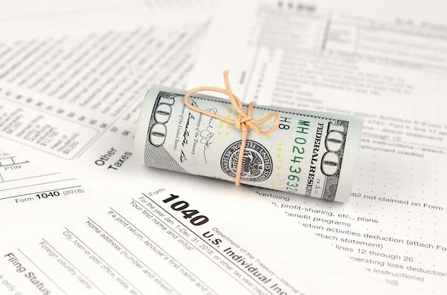 1040 formulário de declaração de imposto de renda individual com rolo de notas de dólar americano