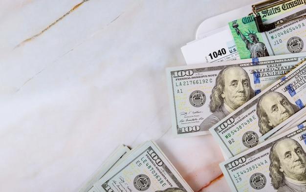 1040 formulário de imposto com cheque de reembolso e moeda close-up de notas de dólar