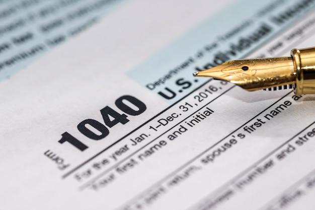 1040 formulário de imposto individual com caneta na mesa de madeira