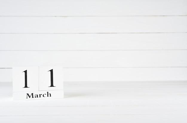 11 de março, dia 11 do mês, aniversário, aniversário, calendário de bloco de madeira sobre fundo branco de madeira com espaço de cópia para o texto.