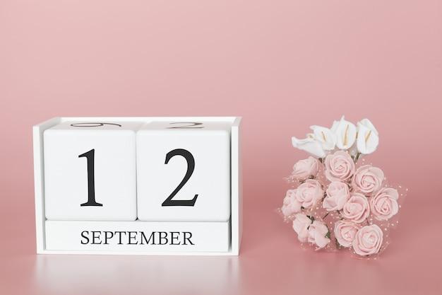 12 de setembro. dia 12 do mês. calendar o cubo no fundo cor-de-rosa moderno, no conceito do negócio e em um evento importante.