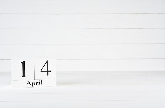 14 de abril, dia 14 do mês, aniversário, aniversário, calendário de bloco de madeira no fundo de madeira branco com espaço da cópia para o texto.