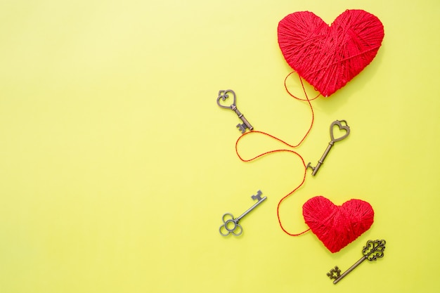 14 de fevereiro, chaves com o coração como um símbolo do amor. cartão com coração vermelho na parede amarela. parede de dia dos namorados. chave do meu conceito de coração. caminho para o coração. dia dos namorados. copie o espaço