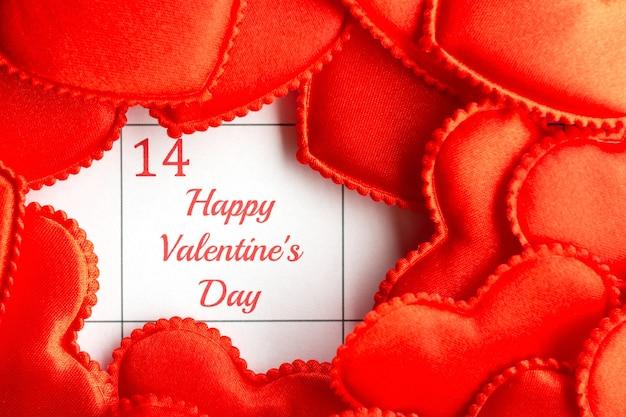14 de fevereiro, dia dos namorados. corações de pano vermelhos no calendário