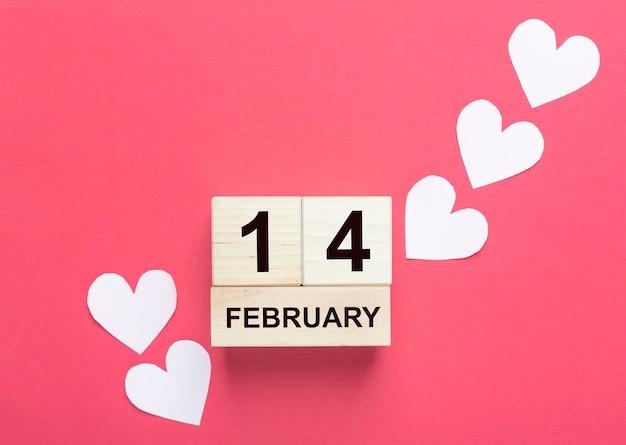 14 de fevereiro em um calendário de madeira com corações rosa pálido sobre fundo vermelho.