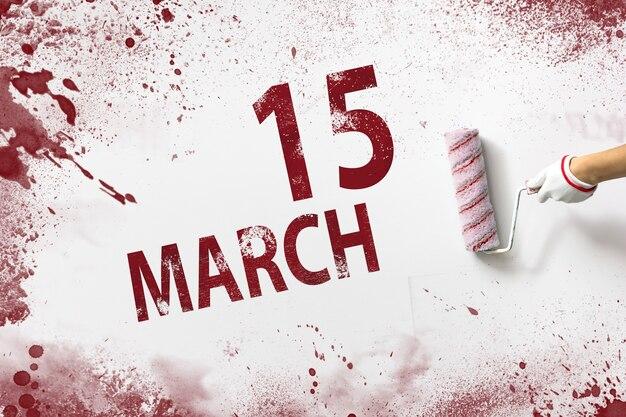 15 de março. dia 15 do mês, data do calendário. a mão segura um rolo com tinta vermelha e escreve uma data do calendário em um fundo branco. mês de primavera, dia do conceito de ano.