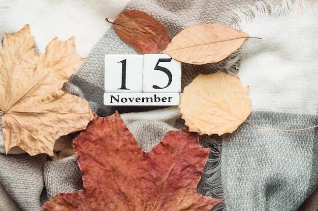 15 de novembro em calendário de cubos brancos sobre manta com folhas. postura plana