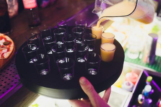 17 bebida alcoólica em copos de shot com fatias de laranja na mesa de madeira.