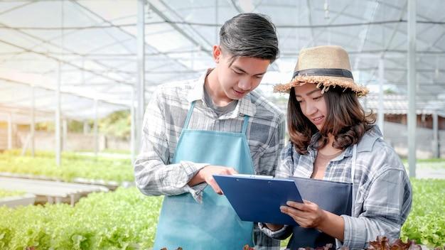 2 agricultor inspeciona a qualidade da salada de vegetais orgânicos e alface da fazenda hidropônica e faz anotações na prancheta